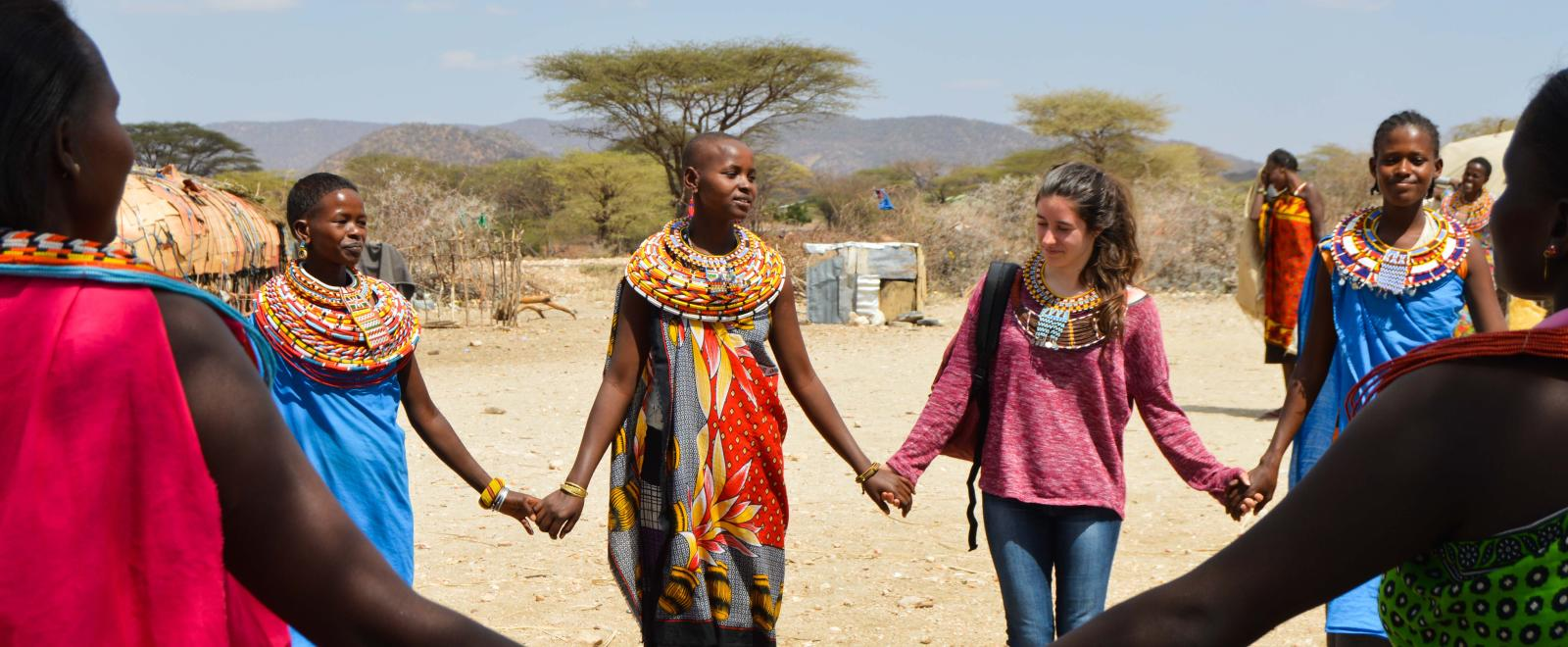 traveller holds hands with a Samuru tribe member as part of her Discovery Tour in Kenya.